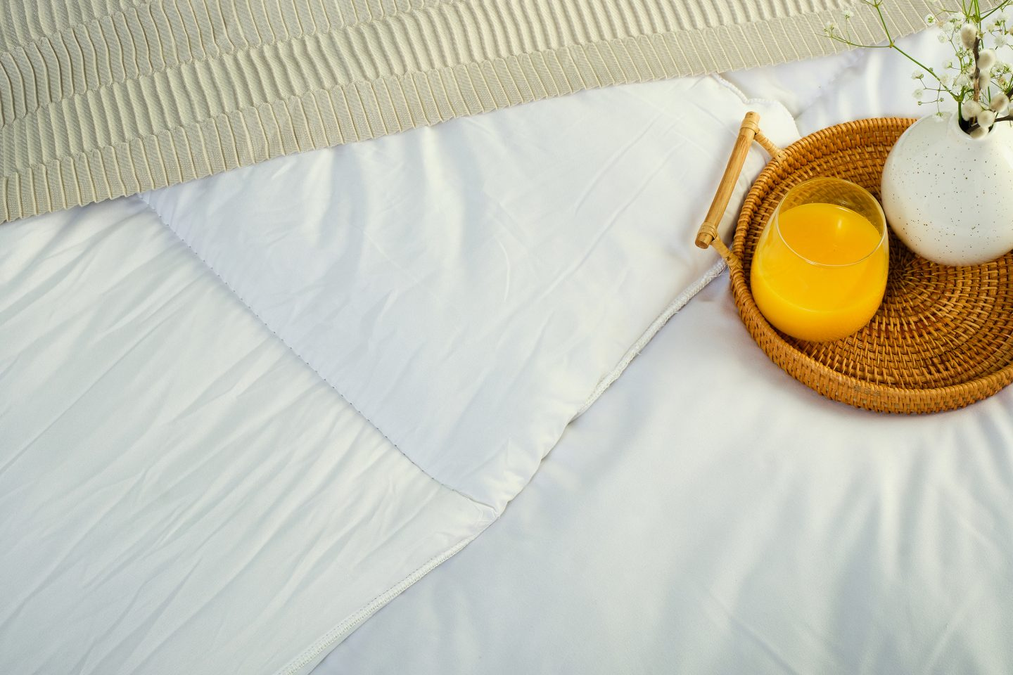 Tray holding an orange juice sat on a duvet