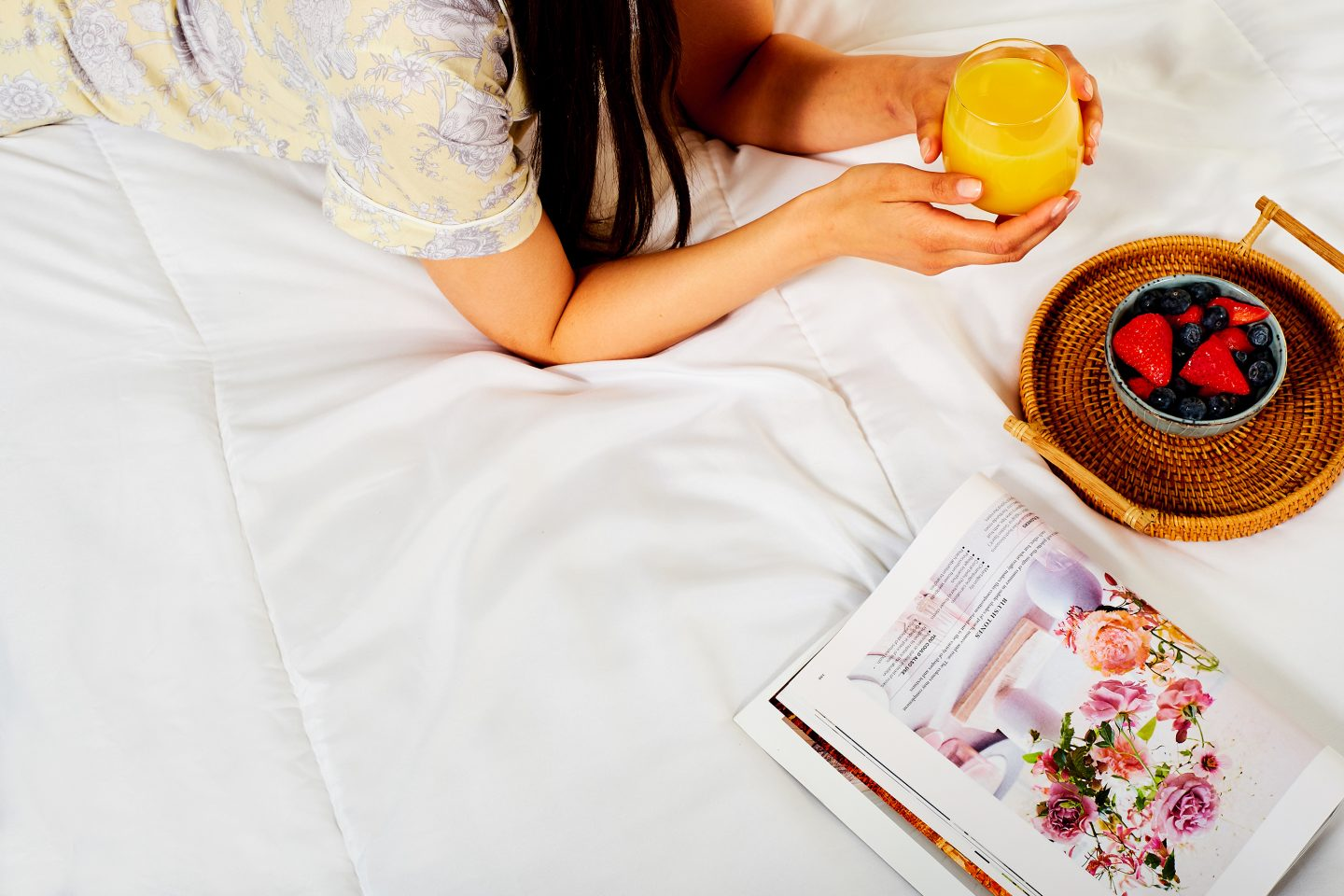 Woman laid on a bed with orange juice and a bowl of fruit