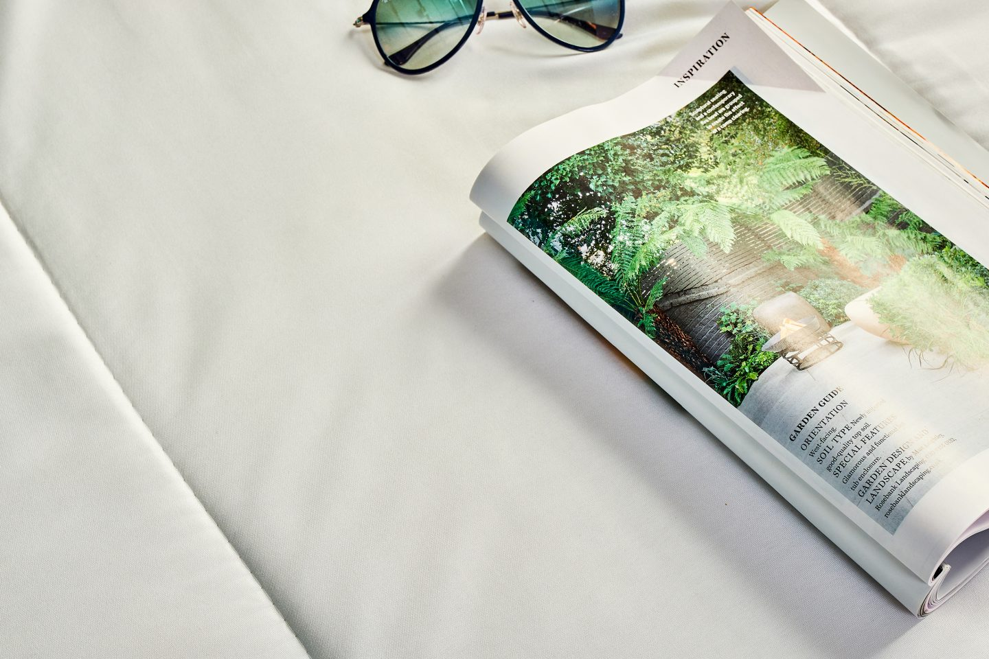 A magazine and sun glasses on a duvet
