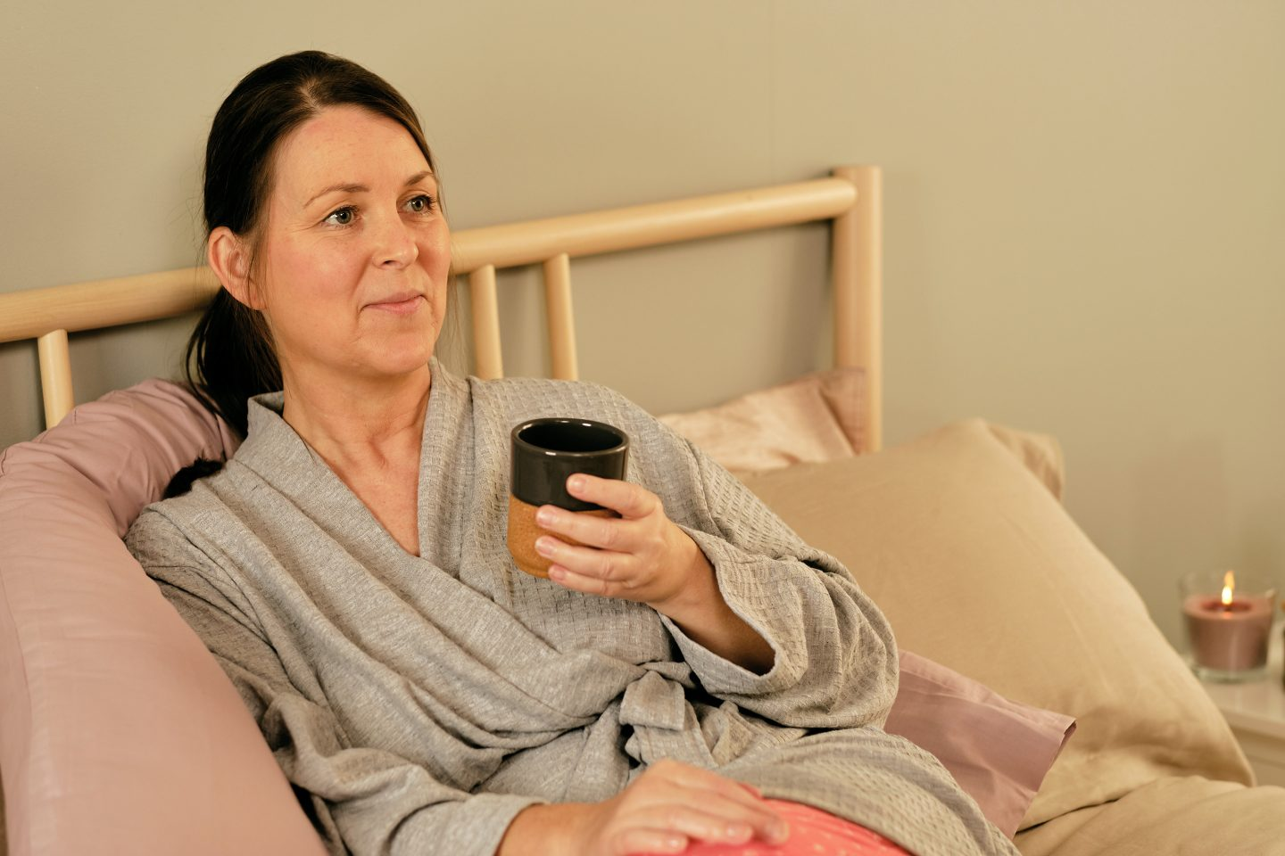 Woman sat in bed with a coffee